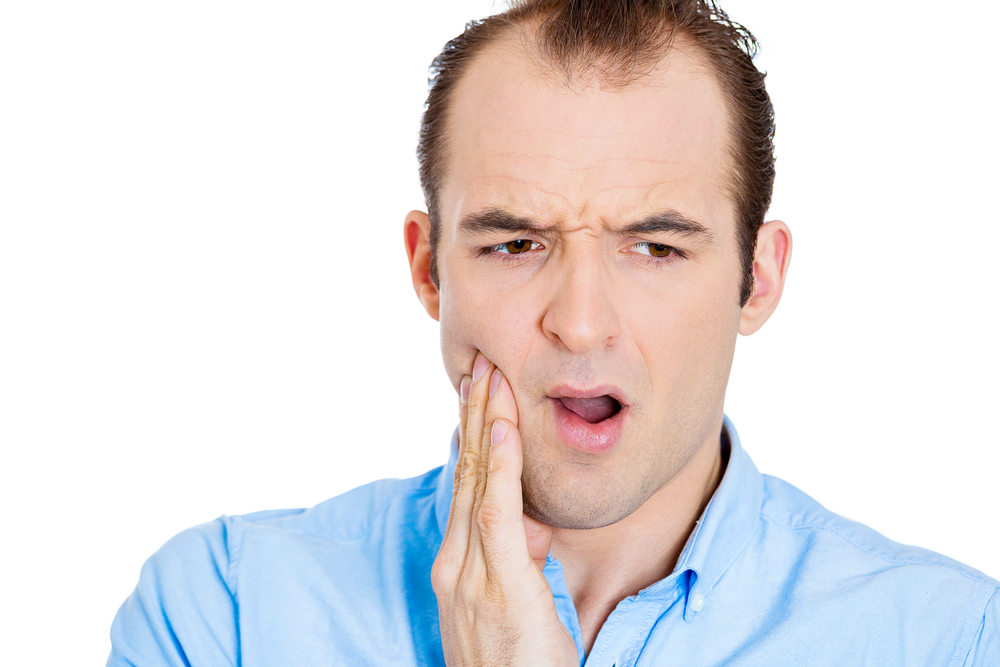 Closeup portrait of young man with sensitive tooth ache crown problem, suffering from pain, touching outside mouth with hand, isolated white background. Negative emotions, facial expression, feeling